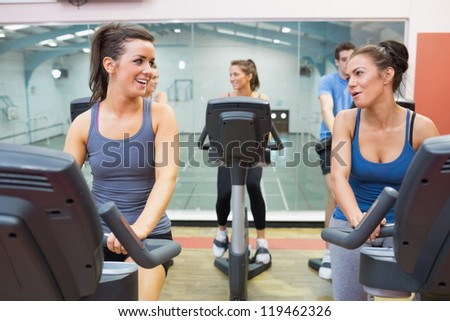 Two women talking while training in a spinning class in gym - stock photo