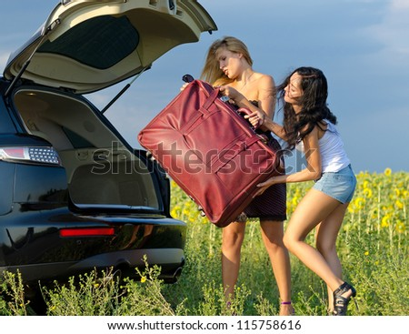 Two women tourists loading a heavy bag into the back of an estate car with the boot open near a field of sunflowers - stock photo
