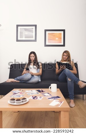 two women using mobile and reading a book on sofa in her home - stock photo