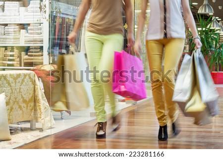 Two women walking along shop windows with shopping bags in hands - stock photo