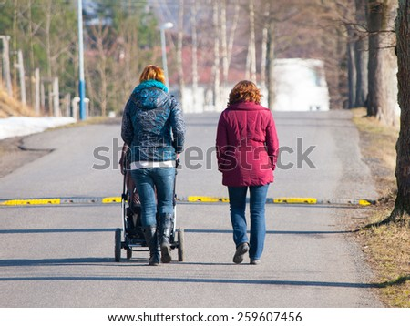 Two women walking towards speed bump with pram in sunny day - stock photo