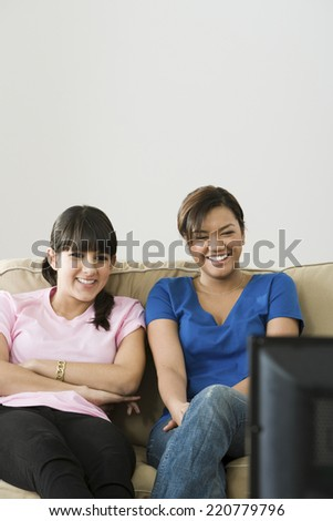 Two women watching television together on a sofa - stock photo