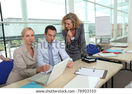two women wearing suits and a man are working in a company