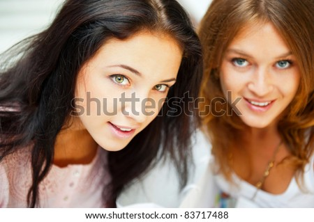 Two women whispering and smiling while shopping inside mall - stock photo