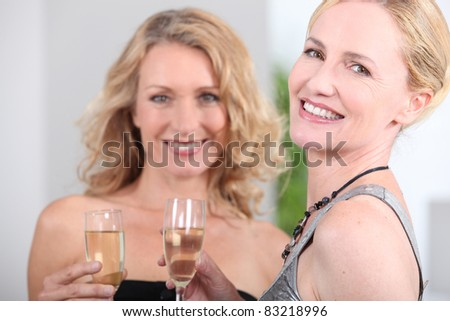 Two women with champagne flutes - stock photo