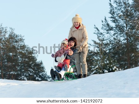 Two women with child sliding on sleds downhill in winter - stock photo