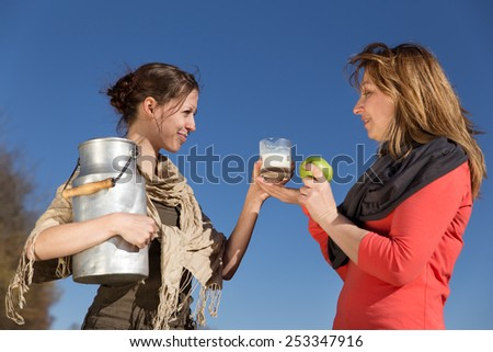 Two women with healthy food are smiling to each other - stock photo