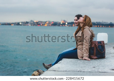 Two Women with Istanbul Cityscape on Background at Dusk - stock photo