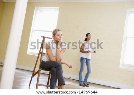 Two women with ladder in empty space holding paper - stock photo