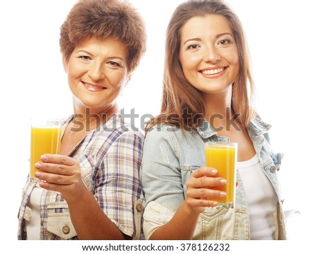 Two women with orange juice. Mother and Daughter - happy family. - stock photo
