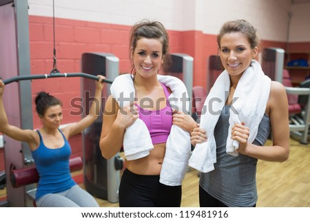 Two women with towels with woman using weight machine in gym - stock photo