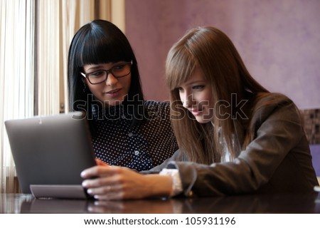 two women work with laptop in coffee - stock photo