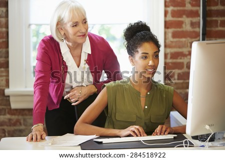 Two Women Working At Computer In Contemporary Office - stock photo