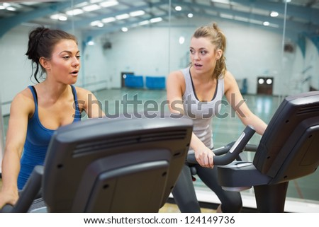Two women working out on exercise bikes in gym - stock photo