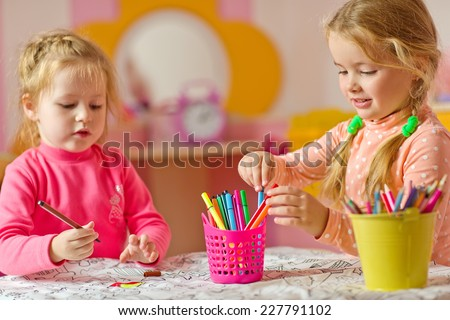 Two wonderful children draw with colored pencils - stock photo