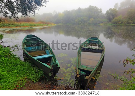 Two wooden boats on morning river - stock photo