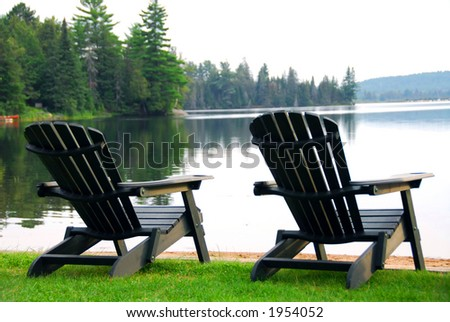 Two wooden chairs on a lake shore in the evening - stock photo