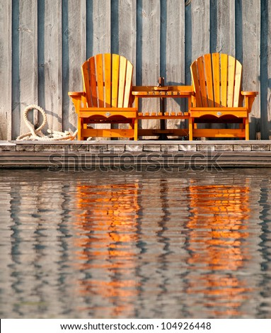 Two wooden chairs reflected in the water