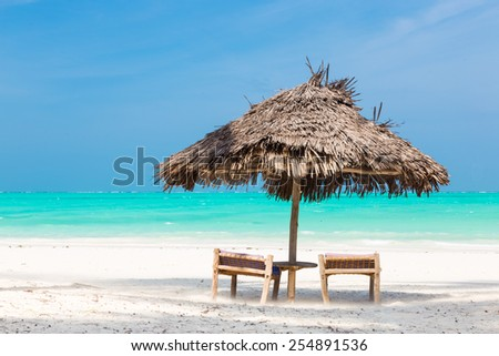 Two wooden dack chairs and umbrella on stunning tropical beach. Turquoise blue lagoon of Paje beach, Zanzibar, Tanzania. - stock photo