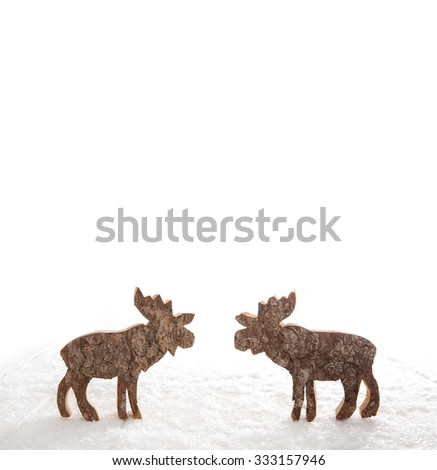 Two wooden handmade reindeer isolated on white background with snow for christmas decoration. - stock photo