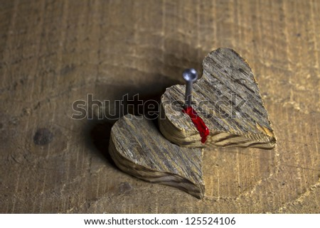Two wooden heart nailed and bleeding on wooden background - stock photo