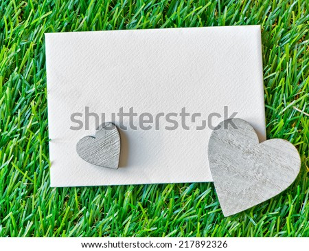 Two Wooden Hearts and Blank Paper Note on Green Grass as seen from Above - stock photo