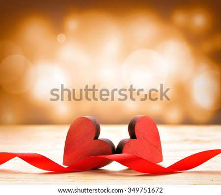 Two wooden hearts and red ribbon. Background for Valentines Day. - stock photo