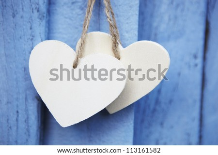 Two Wooden Hearts Hanging On Blue Wooden Surface - stock photo
