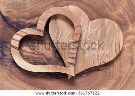 two wooden hearts on a wooden background, olive wood, horicontal, text happy valentines day - stock photo