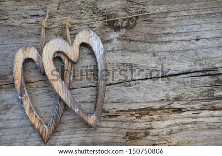 Two wooden hearts on old wooden board, background, text area - stock photo