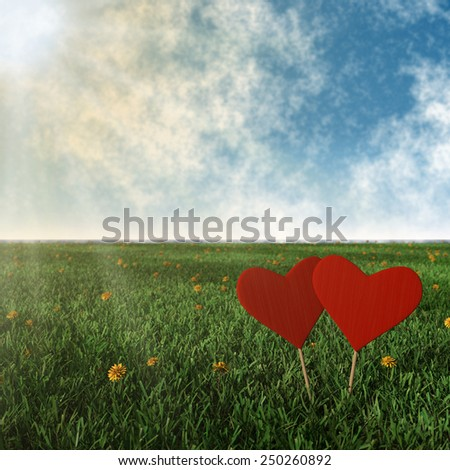 two wooden hearts with grass, sun and blue sky background - stock photo