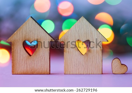 Two wooden houses with hole in the form of heart with little heart on colorful bokeh background