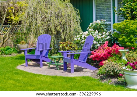 Two  wooden lawn chairs at the front, back yard. Landscape design. - stock photo