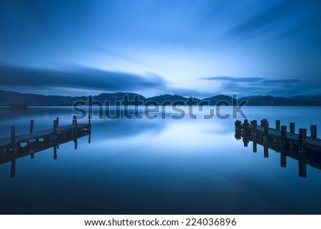 Two Wooden pier or jetty on a blue lake sunset and cloudy sky reflection on water. Long exposure, Versilia Massaciuccoli Lake, Tuscany, Italy. - stock photo