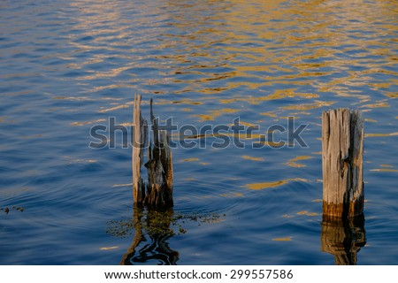 two wooden pilings at sundown - stock photo