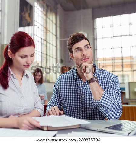 Two work colleagues sitting brainstorming together on a new project with the handsome young man sitting looking contemplatively into the air - stock photo