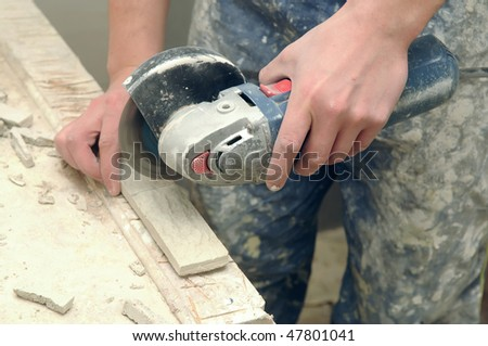 two worker hands cutting the stone tile by circular saw