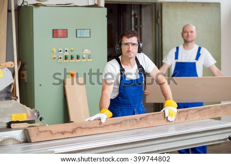two worker in a carpenter's workshop using saw machine - stock photo