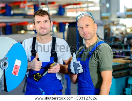 two worker in factory on the machinewith thumb up