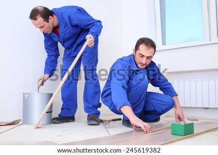 Two workers apply glue to the board with a spatula and put them on the floor - stock photo