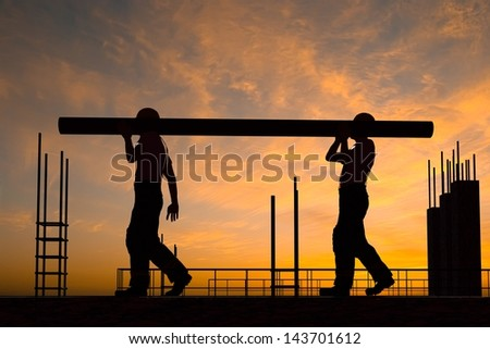 Two workers carry a pipe. - stock photo
