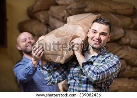 Two workers carrying the bags of cement at the construction site  - stock photo