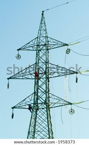 Two workers connecting wires on electrical pylone - stock photo