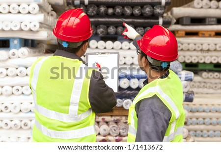 Two workers factory textile inspecting and checking raw material fabrics in warehouse - stock photo