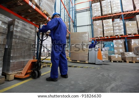 Two workers in uniforms and safety helmets working in storehouse - stock photo