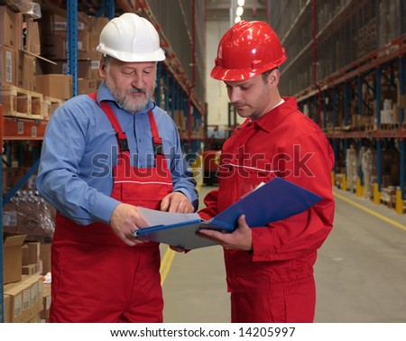 two workers in uniforms in warehouse reviewing papers - stock photo