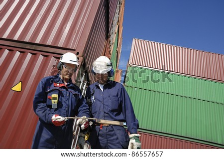 two workers inside busy container-port, stacks of cargo-containers in background - stock photo