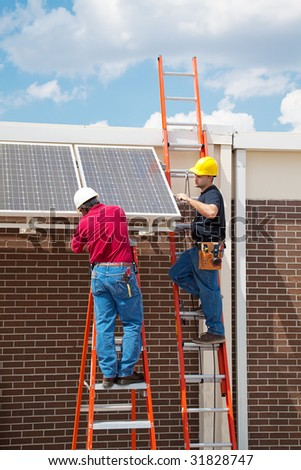 Two workers installing solar panels on the side of a building.  Vertical with room for text. - stock photo