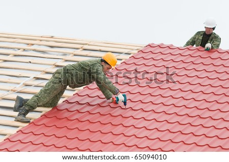 two workers on roof at work screw driving metal tile and roofing iron - stock photo