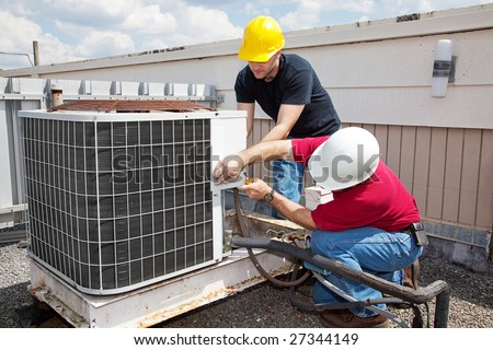Two workers on the roof of a building working on the air conditioning unit. - stock photo